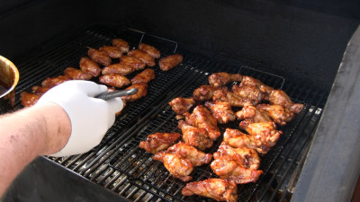 SmokingPit.com - Kentucky Bourbon Glazed Chicken Wings.  Slow cooked on the yoder YS640. Mopping on the bourbon sauce..