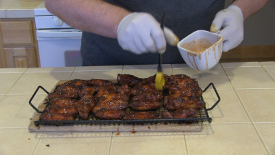SmokingPit.com - Mad Hunky Tiger Sauce Hot Wings.  Slow cooked on the yoder YS640. Applying Tiger Sauce to the wings.