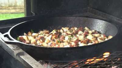 SmokingPit.com - Super moist Orange Chicken with Garlic Red Potatoes cooked on a Scottsdale Santa Maria style cooker over an Oak wood fire. The Scottsdale by Arizona BBQ Outfitters. - Garlic Red Poatatoes in the Lodge cast iron skillet.